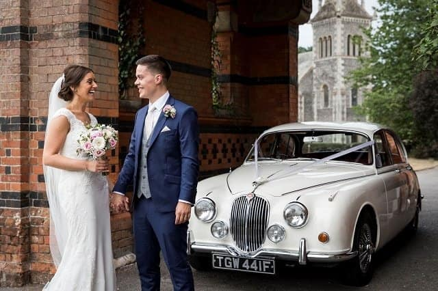 The Bride and Groom at the Elvetham Hotel standing by our classic Jaguar Mk2